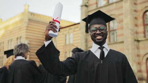Portrait of the African American happy young graduated man posing to the camera and showing his diploma in front of the University. Graduates with professor on the background. Outdoors