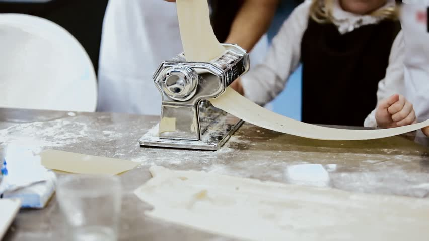 children with their grandmother make sheets of pasta for lasagna. homemade pasta for lasagna on a home machine for lasagna. Making Lasagna sheets at home, flattened dough in pasta machine close-up