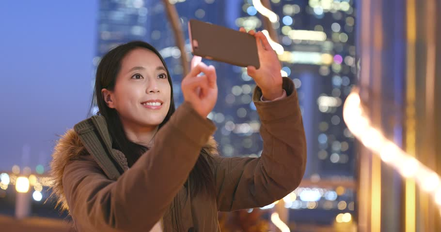 Asian woman taking photo on cellphone in the city of Hong Kong at night, bokeh city background | Shutterstock HD Video #34057930
