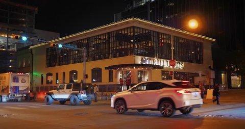 AUSTIN, TX - Circa December, 2017 - A nighttime establishing shot of a corner bar/restaurant on West 4th Street in downtown Austin, Texas. Day/night matching available.