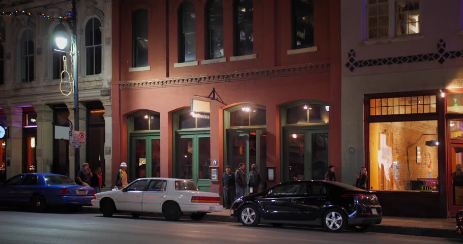 AUSTIN, TX - Circa December, 2017 - A nighttime establishing shot of bars and restaurants on E 6th Street in the historic tourist district of Austin, Texas. Day/night matching available.