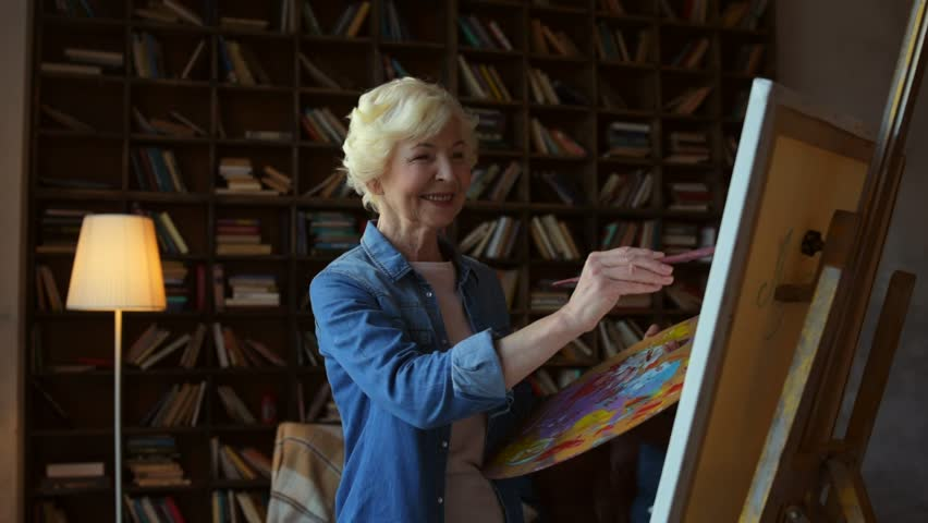 Express your creativity. Positive elderly woman holding a brush and drawing on easel while enjoying her hobby
