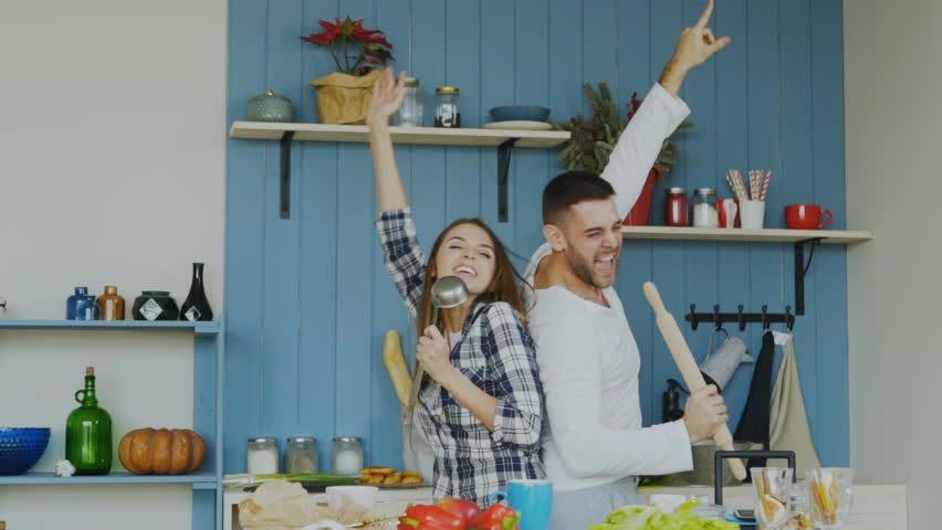 Slowmotion of Young joyful couple have fun dancing and singing while cooking in the kitchen at home #34071550