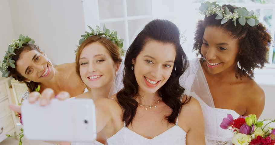 Close-up of bridesmaids and bride making pout while taking a selfie 4K