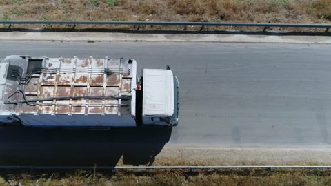 Aerial top-down view flight over road then garbage truck takes over other common names for this type of truck include trash truck rubbish truck waste collection vehicle and refuse collection vehicle