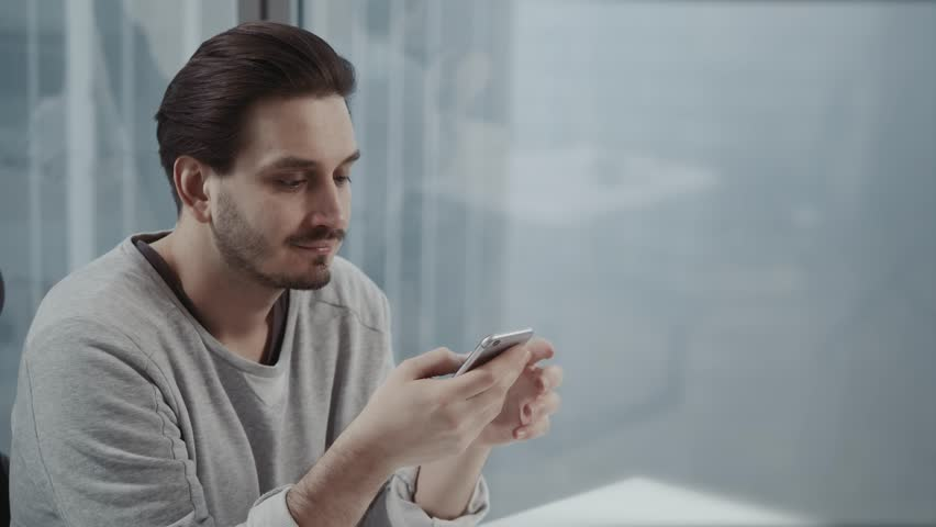 Portrait of young businessman talk on cellphone while stand by his office window in modern interior of skyscraper building, male entrepreneur having mobile phone conversation after important briefing | Shutterstock HD Video #34096870