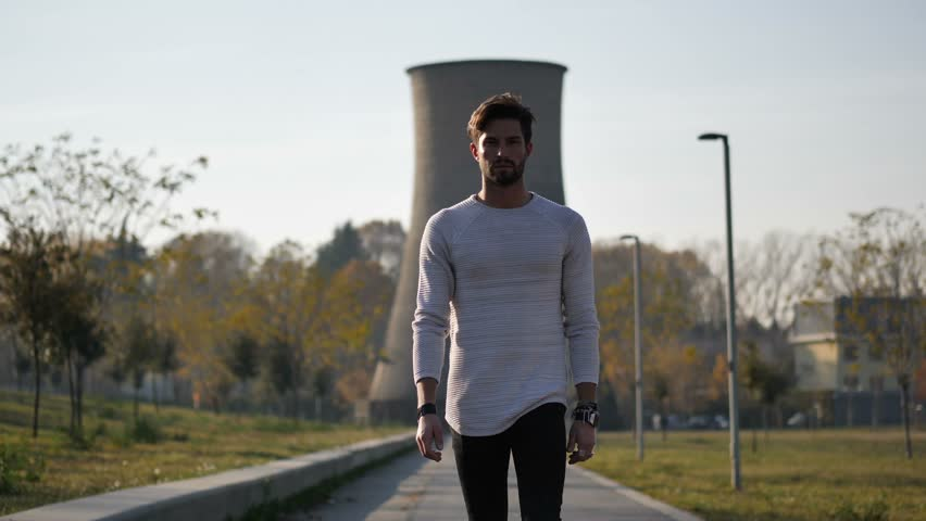 Sexy handsome young man in jeans and white sweater walking in city park | Shutterstock HD Video #34098790