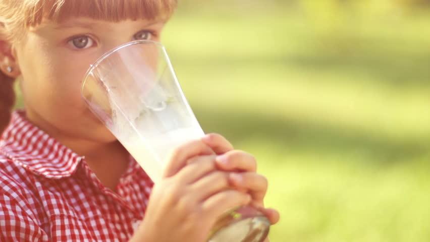 Portrait of smiling girl drinking milk outdoors in sunny lights. Milk mustache.