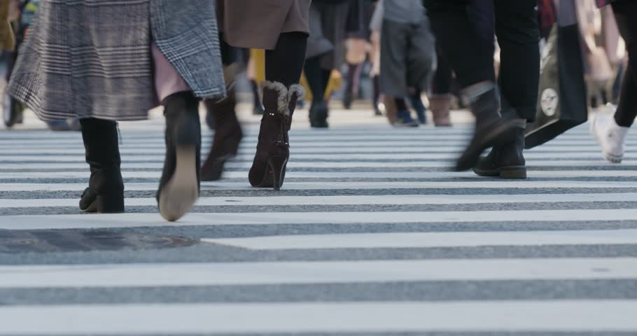 Tokyo / Japan - December 18 2017: People crossing the road in the Shibuya area. Low-angle of feet.