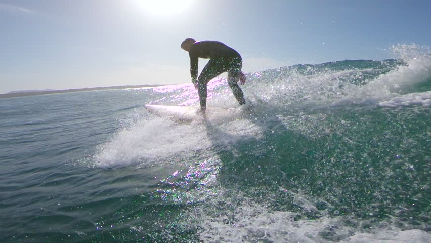 SLOW MOTION, LENS FLARE: Surfboarder riding a small wave on a bright sunny day. Exciting slow motion of male surfer riding wave in the Canary Islands. Intense sunlight reflecting off clear blue ocean | Shutterstock HD Video #34135090