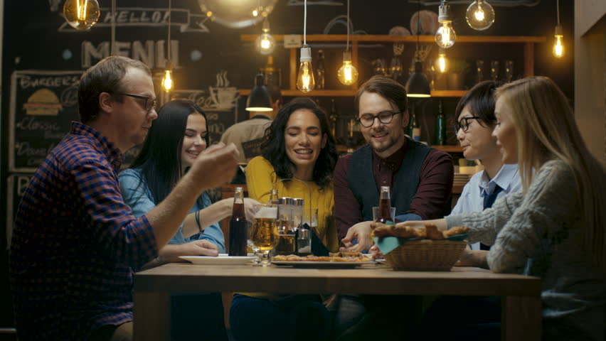 In the Bar/ Restaurant Group of Diverse Young People Eat Slices of Pizza Pie. They Talk, Tell Jokes and Have Fun in This Stylish Establishment.  #34161250