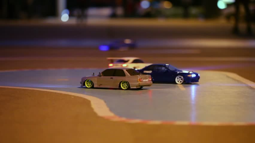 Race of toy cars with radio control on asphalt at evening, closeup
