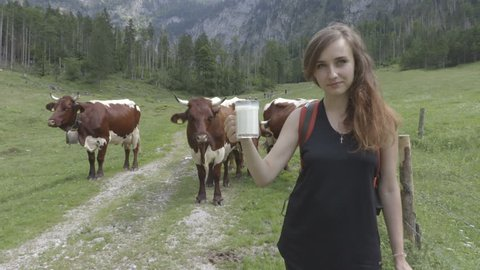 Woman is trying fresh milk from the cow in the mountains