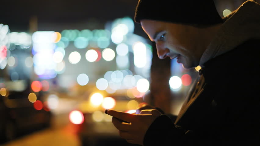 Man holding using smart phone mobile outside standing smiling night city colored bokeh blurred traffic background reading internet surfing glad emotional face closeup 3g application notification