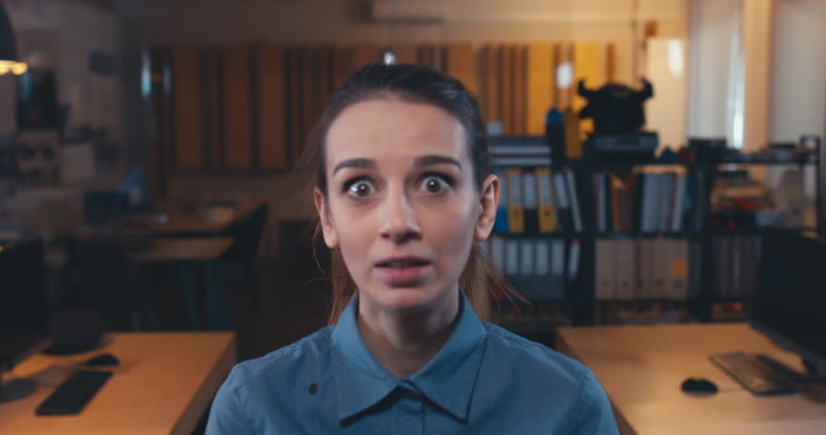 DOLLY IN Portrait of female showing exaggerated surprise facial expression in modern office. 4K UHD