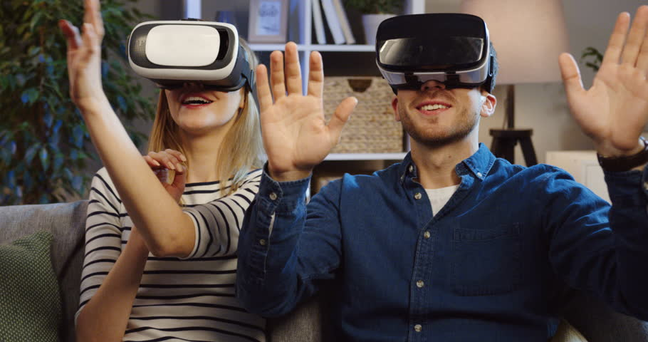 Close up of the young couple wearing VR glasses sitting on the couch in the living room and having VR headset with many emotions, waving their hands in the air. Evening time. Portrait. Indoor