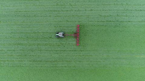 Aerial top-down view of green grass farm field with tractor raking grass so grass can dry faster and becomes dried grass or hay then be picked up and kept for cattle fodder for winter food 4k quality