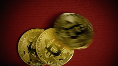 Throwing three golden bitcoins (digital virtual crypto-currency) on a red surface.