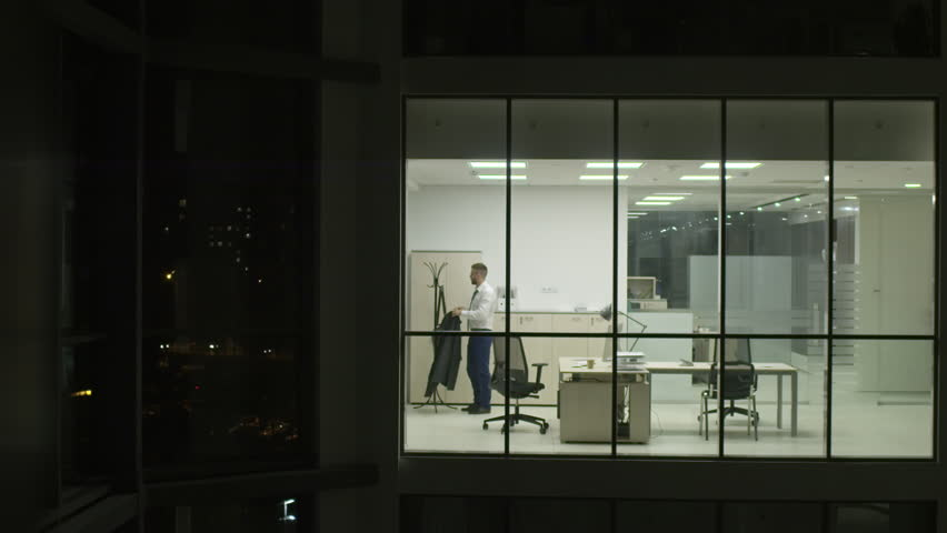 View from outside of modern glass building of businessman entering office, turning on light and start working on computer at night