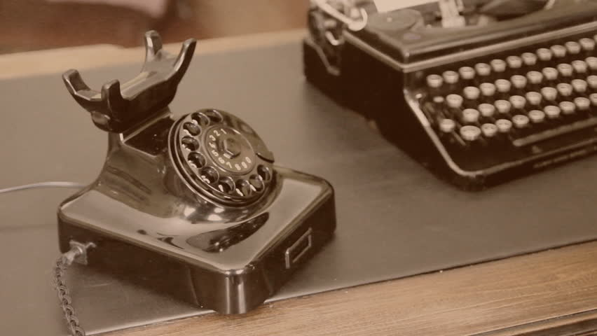 Desk. Vintage typewriter, old phone.