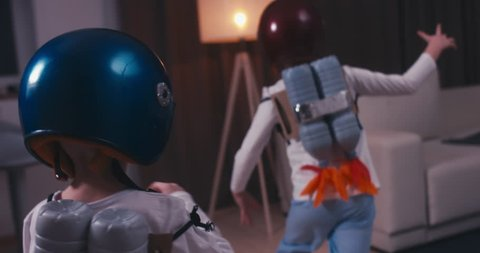 Funny cute dreamer siblings wearing helmets and rocket packs made from plastic bottles pretending to be astronauts, jumping from sofa. 4K UHD 60 FPS SLO MO