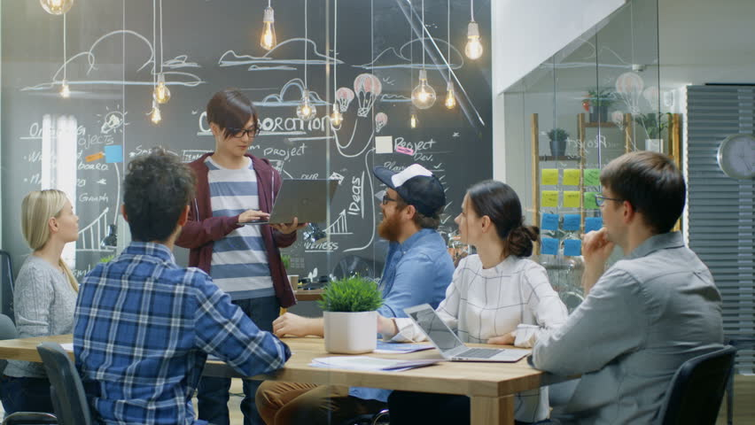 Charismatic Asian Team Leader Shows Laptop to a Diverse Group of Talented Young Developers, They Start Discussion at the Meeting Table. Creative People in Stylish Office Environment. 4K UHD.