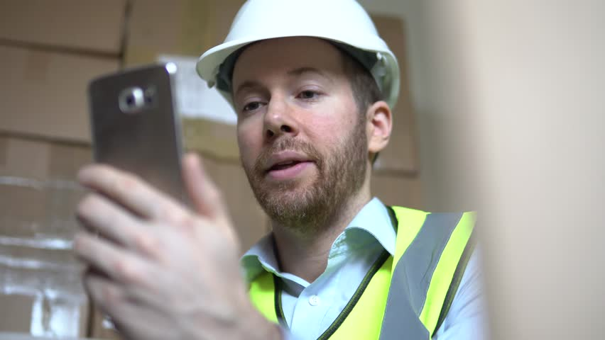 A Distribution Manager Has Mobile Phone Video Call Regarding Delivery In Warehouse. Professional Male Using Smartphone Technology At The Workplace.