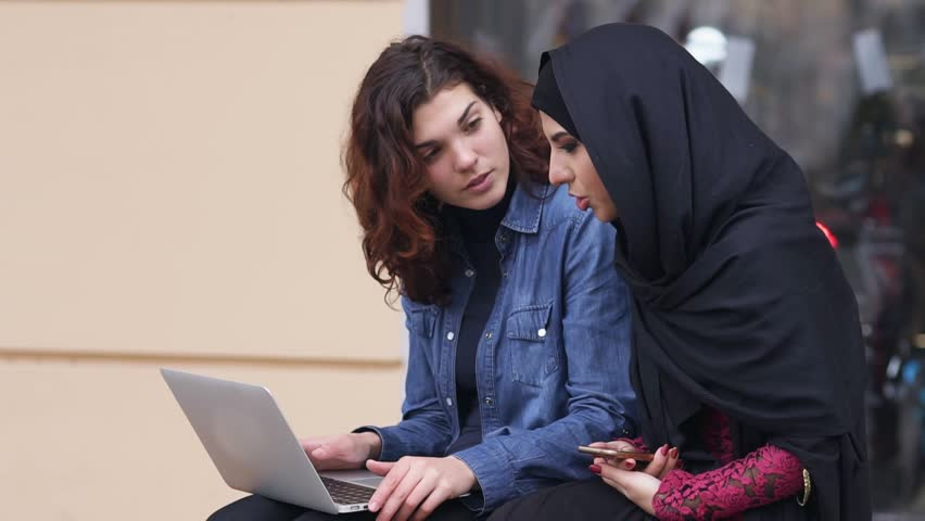 Two female friends sitting outside and using laptop. Cross cultural friendship. Young muslim woman in black hijab is talking to her female caucasian friend. Slowmotion shot