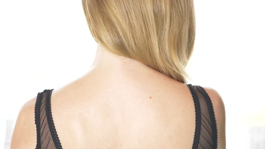 back view, close-up, 4k, slow-motion. a blonde woman takes off a bra strap with one shoulder.