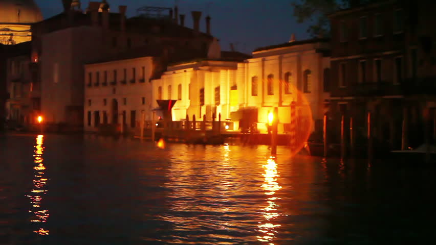 Approaching large structures of Venice by boat at night
