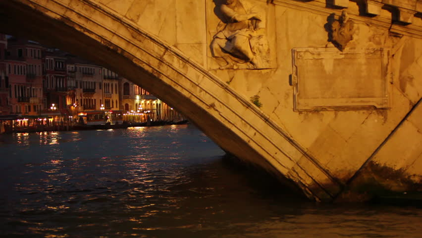 Floating under a bridge revealing low lit buildings in Venice Italy