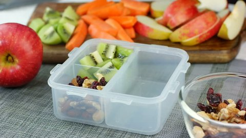 Woman hand put healthy fruit and nut snacks into the lunch box and close it