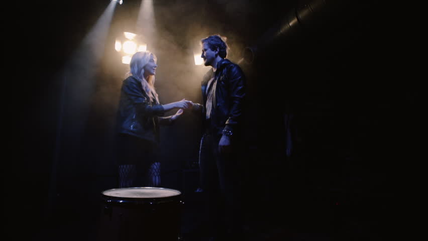 couple in rock-n-roll style, young couple on scene in spotlight kissing at dark background and expression makes the rock n roll gesture
