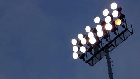 Rack focus of stadium lights in front of a dark blue sky.