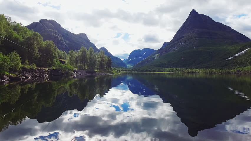 Drone flying through Norways most beautiful mountain valley. Lake reflecting the surreal landscape. Establishing shot.
