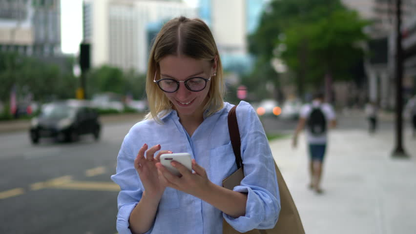 Happy excited young woman receiving discount for shopping while checking email box on mobile calling for sharing success with friend while walking in urban setting down street | Shutterstock HD Video #34497178