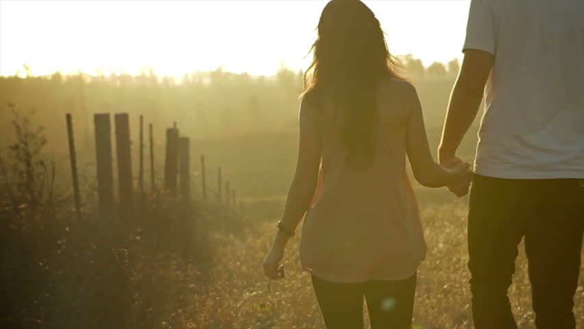 Couple walking in a field and holding hands at sunset. Filmed in slow motion. | Shutterstock HD Video #3452153