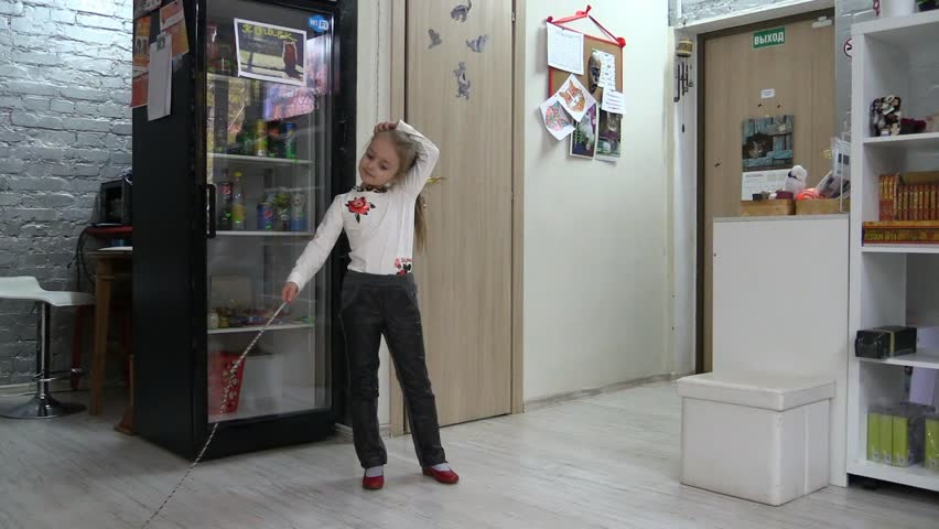 Little girl child joyfully play cat on fishing rod in apartment and afraid a bit