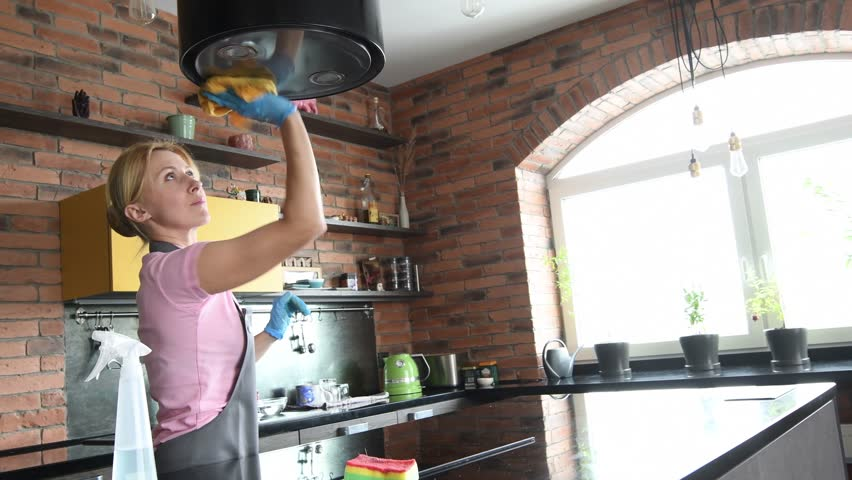 Cleaning service. woman clean cooker at kitchen