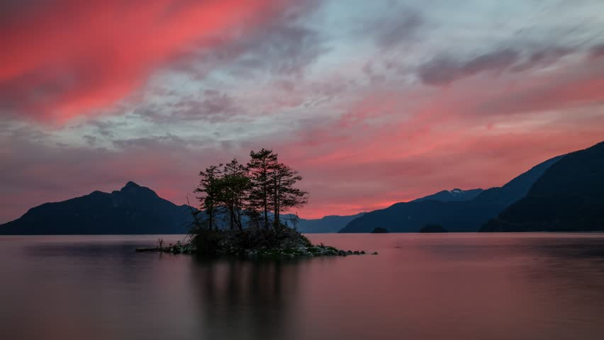 Cinemagraph animation of a beautiful island with mountains in the background during a vibrant sunset. Taken in Howe Sound, North of Vancouver, British Columbia, Canada.
