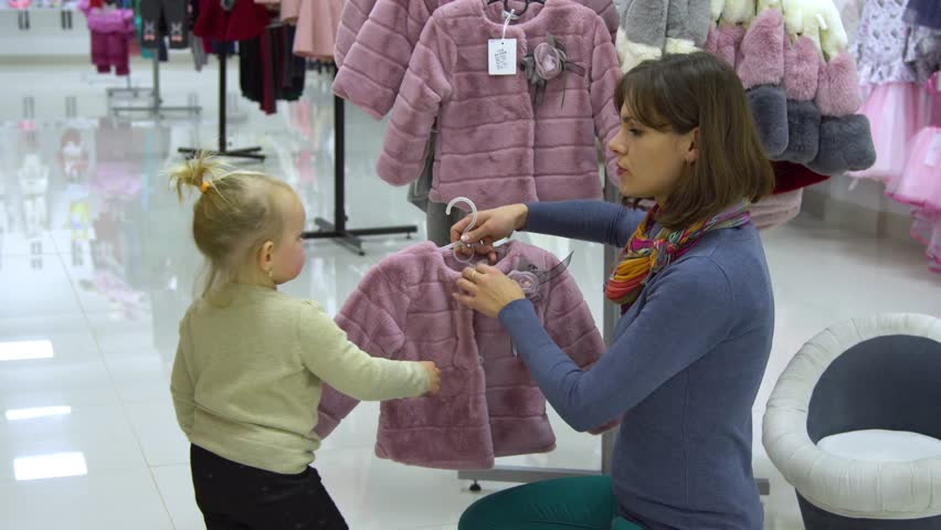 A little sweet girl with her mother chooses children's clothes in a boutique. Mom and child choose clothes in the store. The girl is trying on a pink coat.