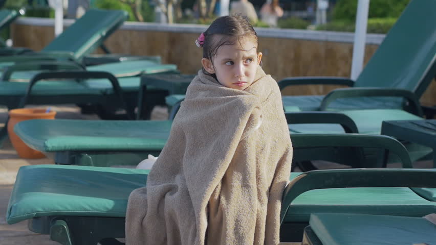 A little girl, wrapped in a towel, with a dirty face, lonely sitting on sitting on a sun lounger by the pool, in the summer. She has a sad look. She wants to sleep | Shutterstock HD Video #34592650