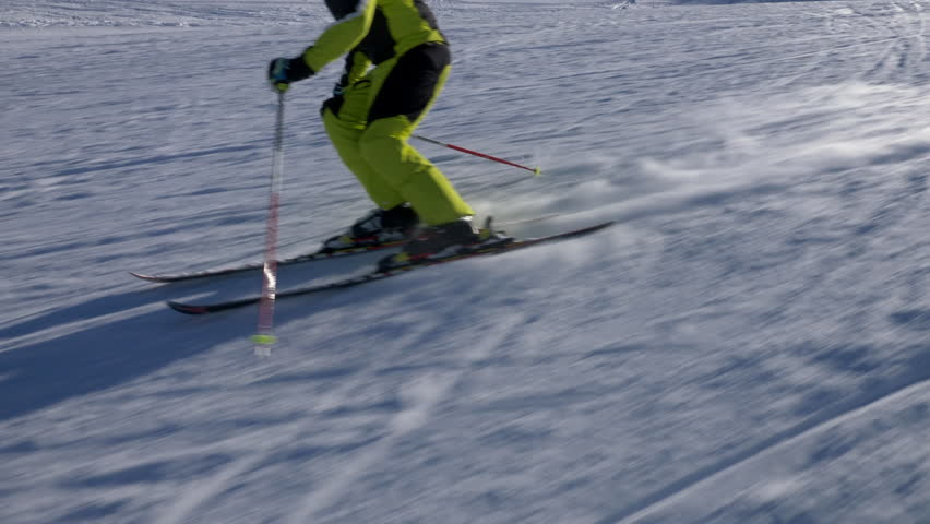 Slow motion - Mid shot of alpine skier doing swings down the ski slope on a sunny winter day