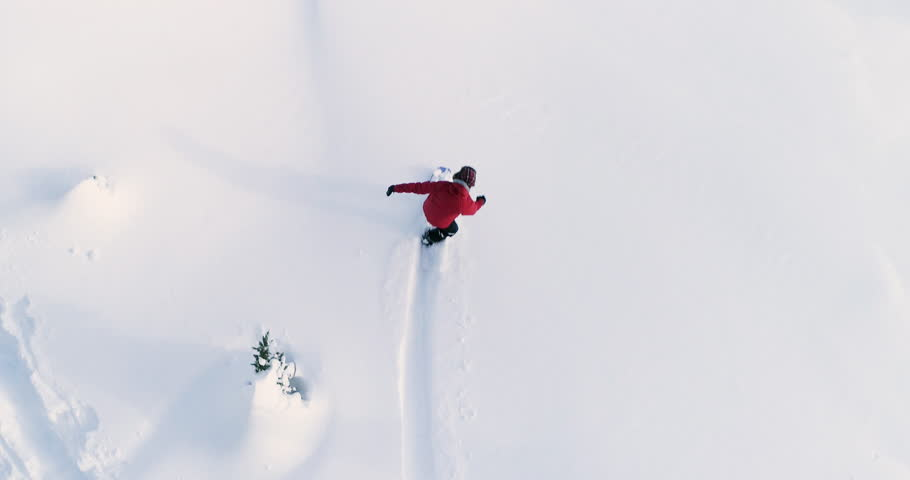 Person Snowboarding Down Slope Drone Aerial Birds Eye View Above White Powder Snow - Winter Extreme Sports Background