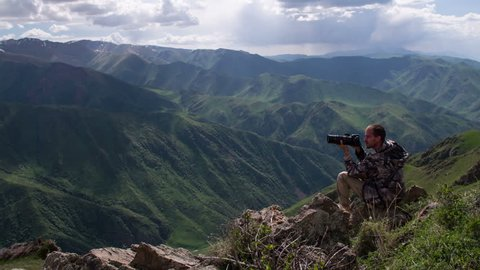 Photographing in the Mountains.  Photographer takes pictures of wildlife in the background spectacular views of the mountain gorge