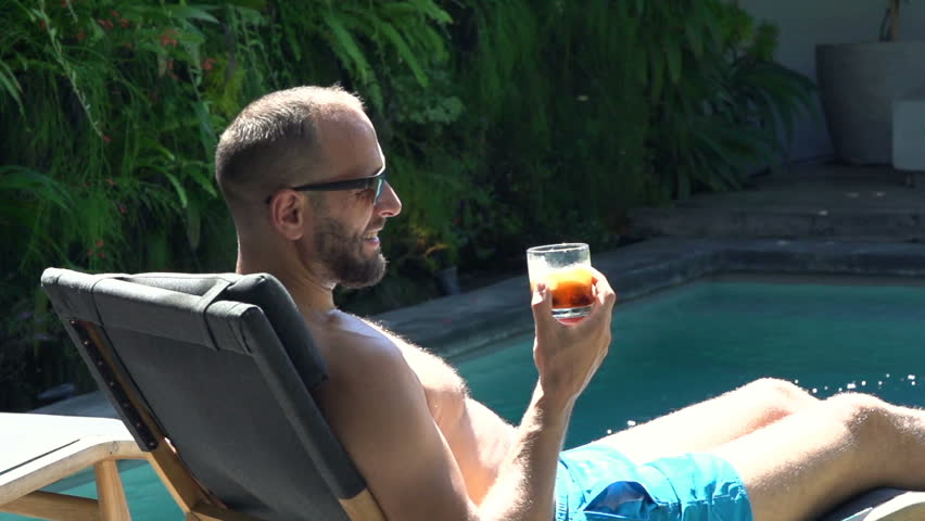 Young man relaxing and drinking whiskey on sunbed by pool