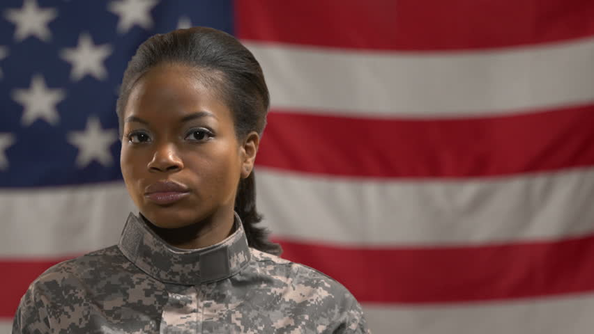 African American female soldier standing in front of American flag