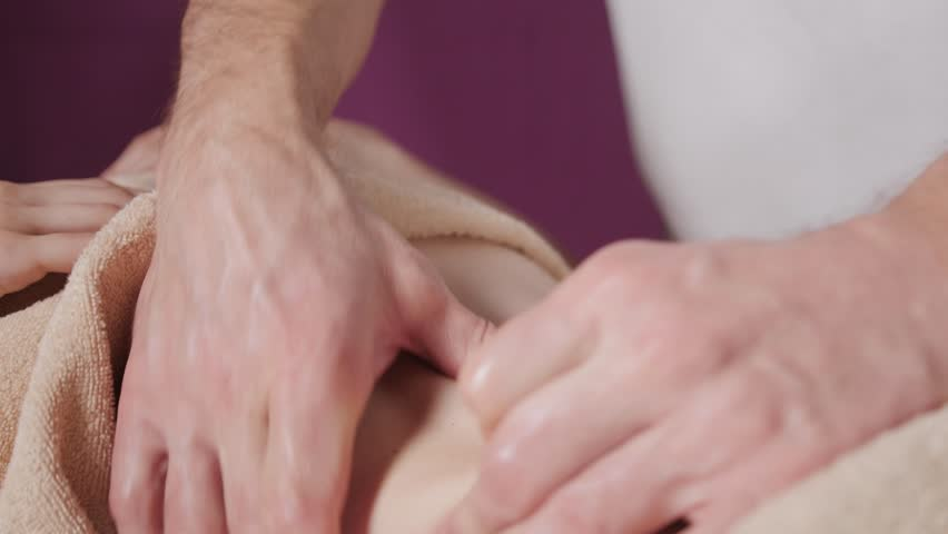 Osteopath doing manipulative massage on female abdomen. Man hands massaging female.Therapist applying pressure on belly. Spa centre concept   Shutterstock HD Video #34644340