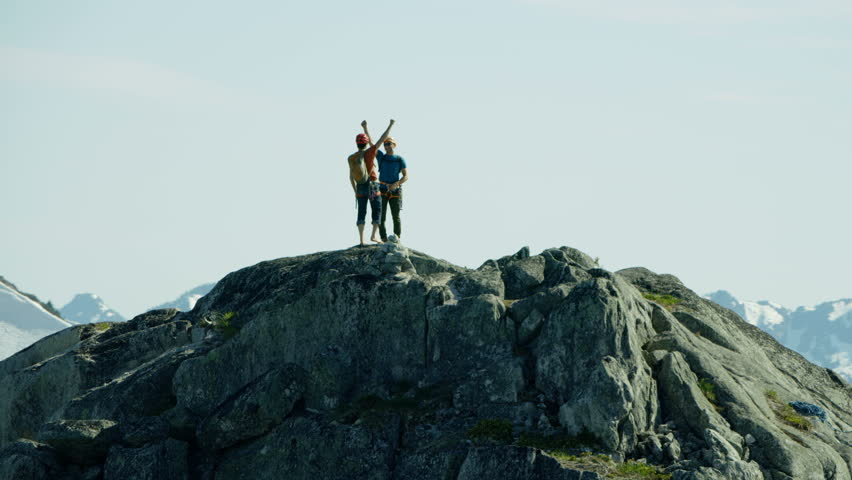 Aerial Caucasian American male adventure climbers with backpack celebrating with raised hands on peak of Mount Habrich Canada RED WEAPON