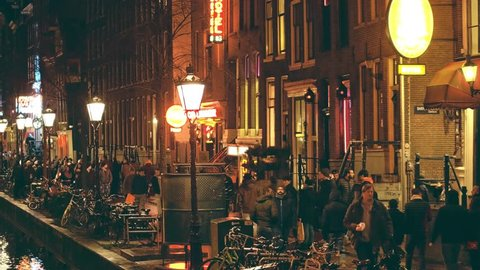AMSTERDAM, NETHERLANDS - DECEMBER 27, 2017. Crowded canal embankment of the red light district De Wallen